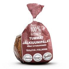 Hannun 100% Gluteeniton Tumma Jälkiuunipala tattarista ruskeassa paperipussissa.